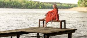 Frau auf Steg am See trägt einen orangefarbenen Bademantel aus Bio-Baumwolle - © Cotonea