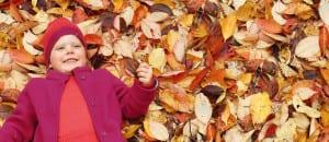 Kind in rot-/lilafarbener Kleidung aus Bio-Strick liegt auf bunten Blättern, © disana
