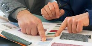 Geschäftspartner besprechen Stoffproben in einem Katalog © Lebenskleidung