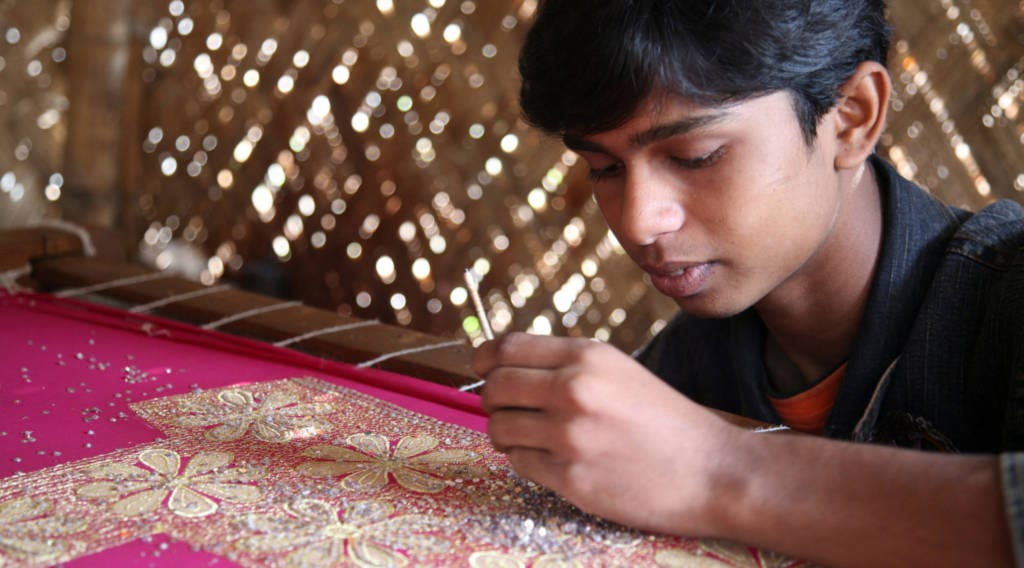 Kinderarbeiter beim Besticken von Kleidung in Indien - child worker embroidering textiles in India
